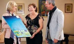 Elaine Madill and visitors viewing some of the art on display at the Wondail Art Gallery